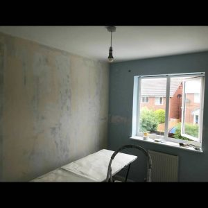 A bedroom before having fresh wallpaper applied